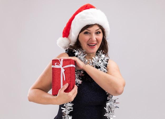 Beeindruckte frau mittleren alters mit weihnachtsmütze und lametta-girlande um den hals, die ein weihnachtsgeschenkpaket hält und die kamera isoliert auf weißem hintergrund mit kopienraum betrachtet