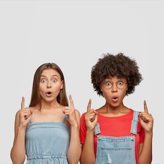 Beeindruckte frauen gemischter rassen zeigen mit beiden zeigefingern nach oben
