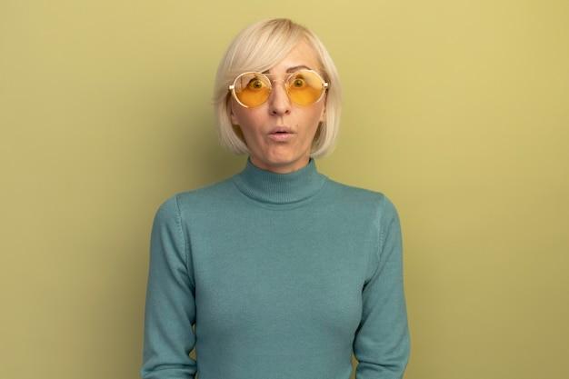 Beeindruckte hübsche blonde slawische frau in der sonnenbrille betrachtet kamera auf olivgrün