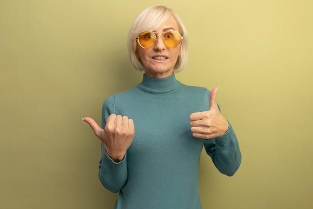 Beeindruckte hübsche blonde slawische frau in sonnenbrille daumen hoch und zeigt seitlich auf olivgrün
