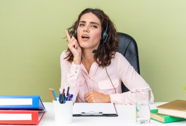 Beeindruckte hübsche kaukasische callcenter-betreiberin auf kopfhörern, die am schreibtisch mit nach oben zeigenden bürowerkzeugen sitzen