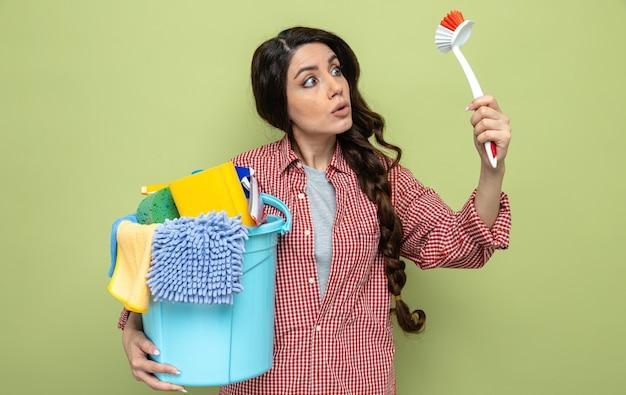 Beeindruckte hübsche kaukasische putzfrau, die reinigungsgeräte hält und bürste anschaut