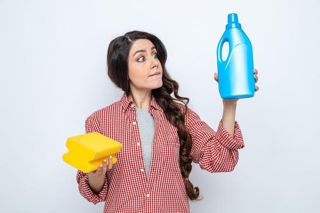 Beeindruckte hübsche kaukasische putzfrau, die toilettenreiniger hält und anschaut und schwamm hält