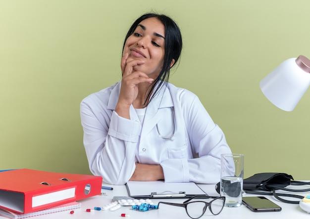Beeindruckte junge ärztin, die ein medizinisches gewand mit stethoskop trägt, sitzt am schreibtisch mit medizinischen werkzeugen, die hand auf das kinn legen, isoliert auf olivgrüner wand
