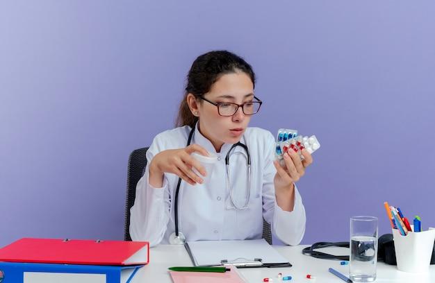 Beeindruckte junge ärztin, die medizinische robe und stethoskop trägt, sitzt am schreibtisch mit medizinischen werkzeugen, die medizinische pillen halten und betrachten und becher isoliert halten