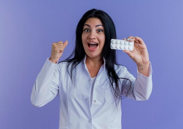 Beeindruckte junge ärztin im medizinischen gewand, die eine packung medizinischer tabletten zeigt und die geballte faust sieht