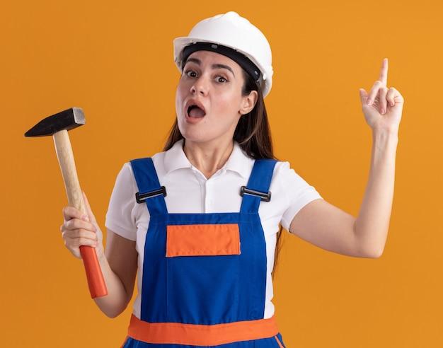 Beeindruckte junge baumeisterin in uniform, die hammerpunkte an oben auf orange wand lokalisiert hält