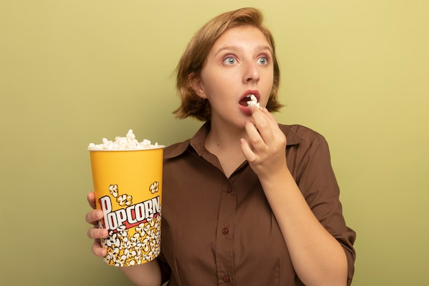 Beeindruckte junge blonde frau, die einen eimer mit popcorn und popcornstück in der nähe des mundes hält und die seite isoliert auf der olivgrünen wand betrachtet