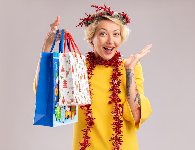 Beeindruckte junge blonde frau, die weihnachtskopfkranz und lametta-girlande um den hals hält, die weihnachtsgeschenktüten hält, die kamera betrachten, die leere hand lokalisiert auf weißem hintergrund zeigt