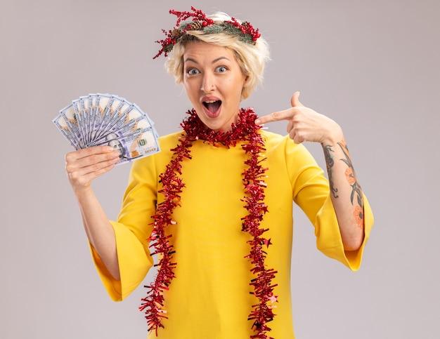 Beeindruckte junge blonde frau, die weihnachtskopfkranz und lametta-girlande um den hals hält und auf geld zeigt, das kamera betrachtet, die auf weißem hintergrund lokalisiert wird