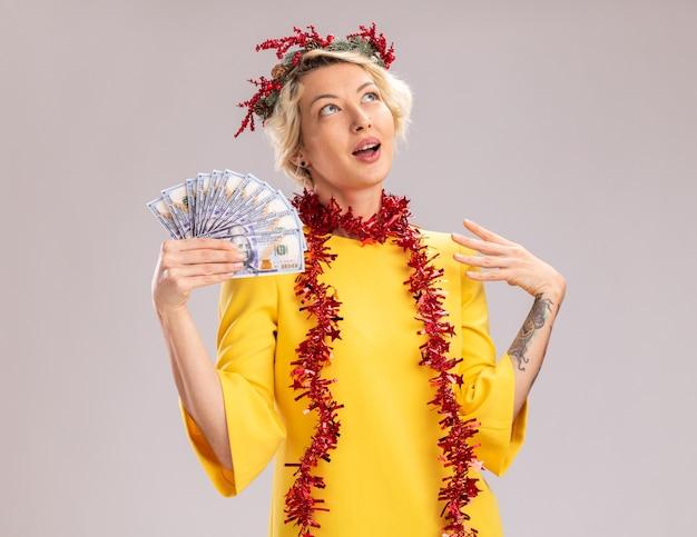 Beeindruckte junge blonde frau, die weihnachtskopfkranz und lametta-girlande um den hals trägt, die geld hält, das hand in der luft hält, die lokal auf weißer wand schaut
