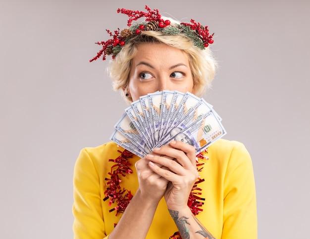 Beeindruckte junge blonde frau, die weihnachtskopfkranz und lametta-girlande um den hals trägt, hält geld, das seite von hinten davon lokalisiert auf weißer wand betrachtet
