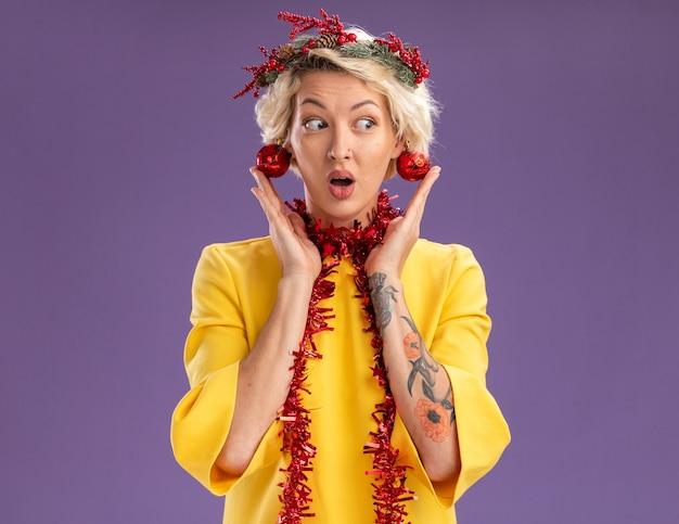 Beeindruckte junge blonde frau, die weihnachtskopfkranz und lametta-girlande um den hals trägt und auf die seite schaut, mit weihnachtskugeln, die von ihren ohren hängen, die kugeln berühren, die auf lila wand mit kopienraum isoliert sind