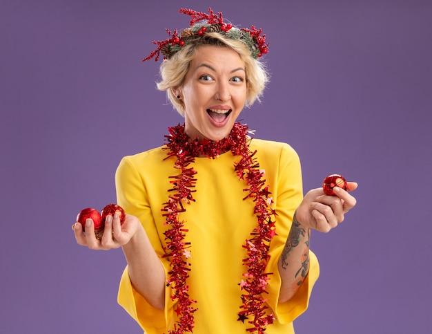 Beeindruckte junge blonde frau, die weihnachtskopfkranz und lametta-girlande um den hals trägt und kamera betrachtet, die weihnachtskugeln lokalisiert auf lila hintergrund hält