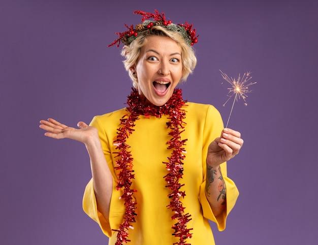 Beeindruckte junge blonde frau, die weihnachtskopfkranz und lametta-girlande um hals hält, die feiertags-wunderkerze hält, die kamera zeigt, die leere hand lokalisiert auf lila hintergrund