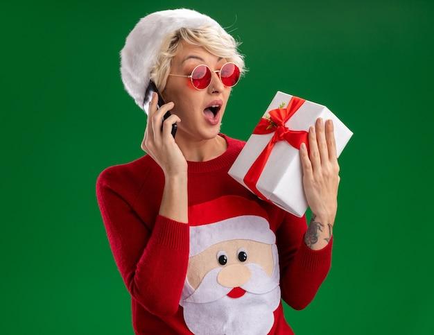 Beeindruckte junge blonde frau, die weihnachtsmütze und weihnachtsmannpullover des weihnachtsmannes mit brille hält, die geschenkpaket hält und betrachtet, das am telefon lokalisiert auf grüner wand spricht