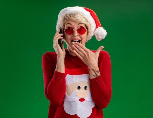 Beeindruckte junge blonde frau, die weihnachtsmütze und weihnachtsmannpullover des weihnachtsmannes mit brille trägt, die am telefon spricht, das kamera betrachtet, die hand auf mund lokalisiert auf grünem hintergrund hält