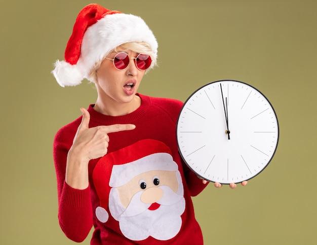 Beeindruckte junge blonde frau, die weihnachtsmütze und weihnachtsmannpullover des weihnachtsmannes mit der brille hält und auf uhr zeigt, die kamera lokalisiert auf olivgrünem hintergrund betrachtet