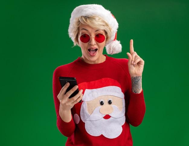 Beeindruckte junge blonde frau, die weihnachtsmütze und weihnachtsmannpullover des weihnachtsmannes mit der brille hält und handy trägt, das oben auf grüner wand mit kopienraum zeigt