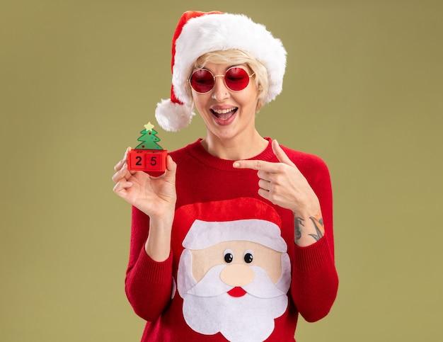 Beeindruckte junge blonde frau mit weihnachtsmütze und weihnachtsmann-weihnachtspullover mit brille, die das weihnachtsbaumspielzeug mit datum isoliert auf olivgrüner wand mit kopienraum betrachtet und zeigt