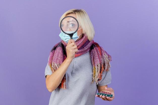Beeindruckte junge blonde kranke slawische frau, die medizinische maske und schal trägt