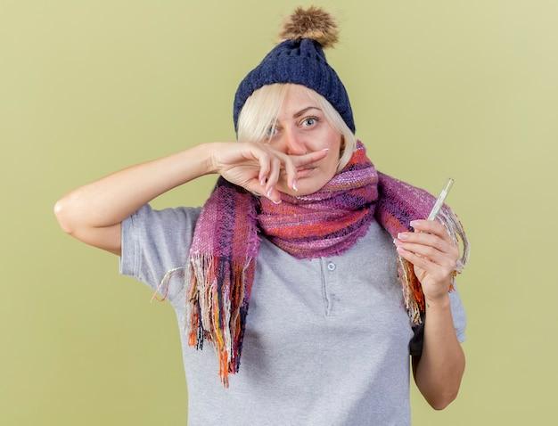Beeindruckte junge blonde kranke slawische frau, die wintermütze trägt