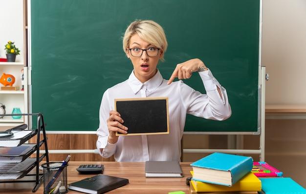 Beeindruckte junge blonde lehrerin mit brille, die am schreibtisch mit schulmaterial im klassenzimmer sitzt und auf die mini-tafel mit blick auf die vorderseite zeigt und zeigt