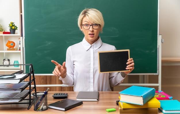 Beeindruckte junge blonde lehrerin mit brille, die am schreibtisch mit schulmaterial im klassenzimmer sitzt und eine mini-tafel zeigt, die auf die vorderseite zeigt, die auf die seite zeigt