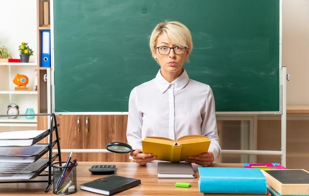 Beeindruckte junge blonde lehrerin mit brille, die am schreibtisch mit schulwerkzeugen im klassenzimmer sitzt und ein offenes buch mit blick auf die kamera hält