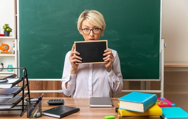 Beeindruckte junge blonde lehrerin mit brille, die am schreibtisch mit schulwerkzeugen im klassenzimmer sitzt und eine mini-tafel mit blick auf die kamera zeigt