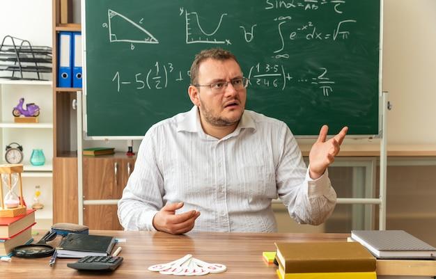 Beeindruckte junge blonde lehrerin mit brille, die am schreibtisch mit schulwerkzeugen im klassenzimmer sitzt und leere hand zeigt, die auf die seite schaut