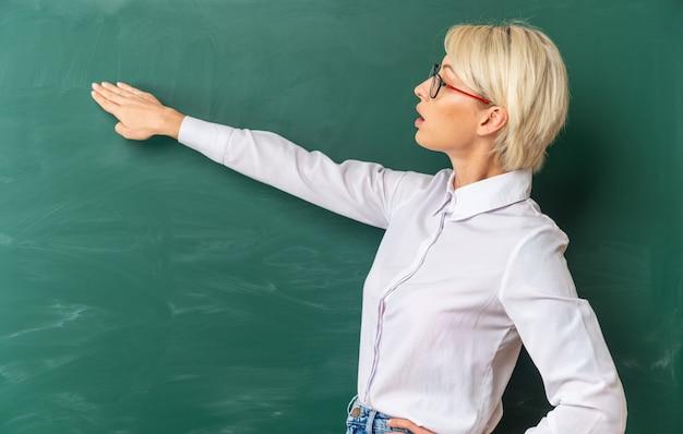 Beeindruckte junge blonde lehrerin mit brille im klassenzimmer, die in der profilansicht vor der tafel steht und auf die tafel mit der hand zeigt, die eine andere hand auf der taille hält