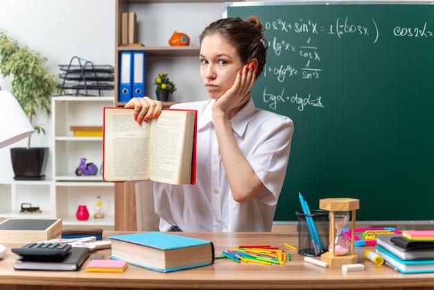 Beeindruckte junge blonde mathematiklehrerin, die am schreibtisch mit schulwerkzeugen sitzt und in die kamera schaut, die buch zur kamera zeigt und die hand im klassenzimmer hält