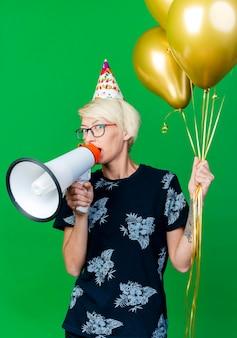 Beeindruckte junge blonde partyfrau, die brille und geburtstagskappe hält, die luftballons hält, die an der front sprechen, die durch sprecher lokalisiert auf grüner wand spricht