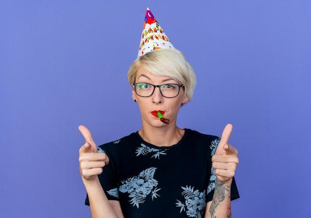 Beeindruckte junge blonde partyfrau, die brille und geburtstagskappe trägt, die front hält partygebläse im mund tut, das sie geste lokalisiert auf lila wand tut