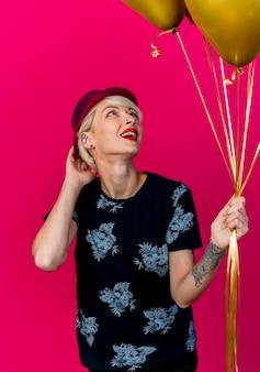 Beeindruckte junge blonde partyfrau, die partyhut hält und ballons berührt, die hut lokalisiert auf rosa wand berühren