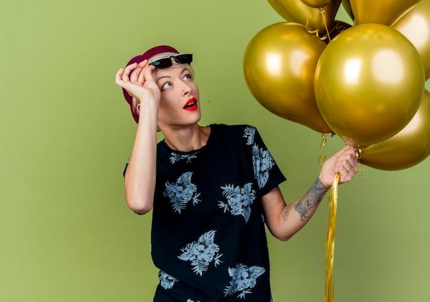 Beeindruckte junge blonde partyfrau, die partyhut und sonnenbrille trägt, die gläser anheben, die luftballons betrachten, die auf olivgrüner wand lokalisiert werden