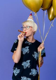Beeindruckte junge blonde partygirl, die brille und geburtstagskappe hält, die ballons hält, die partybläser lokalisiert auf lila hintergrund blasen und betrachten