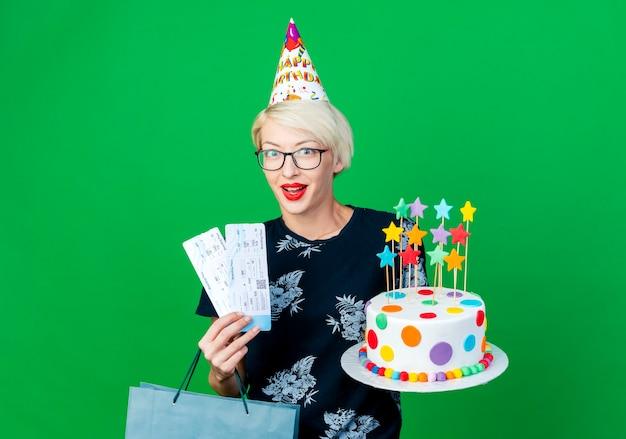 Beeindruckte junge blonde partygirl, die brille und geburtstagskappe hält, die geburtstagstorte mit sternenflugzeugtickets und papiertüte hält, die kamera lokalisiert auf grünem hintergrund mit kopienraum betrachtet