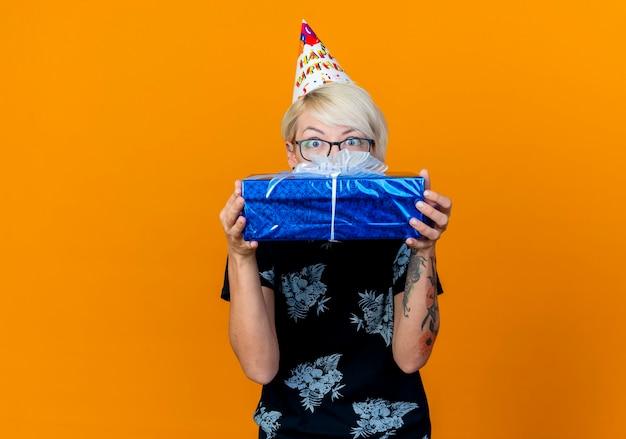 Beeindruckte junge blonde partygirl, die brille und geburtstagskappe hält, die geschenkbox hält, die kamera von hinten lokalisiert auf orange hintergrund mit kopienraum betrachtet