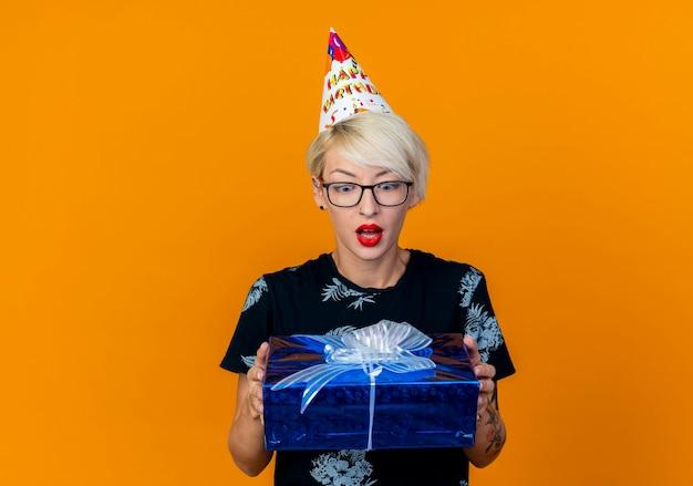 Beeindruckte junge blonde partygirl, die brille und geburtstagskappe hält und geschenkbox lokalisiert auf orange hintergrund mit kopienraum hält