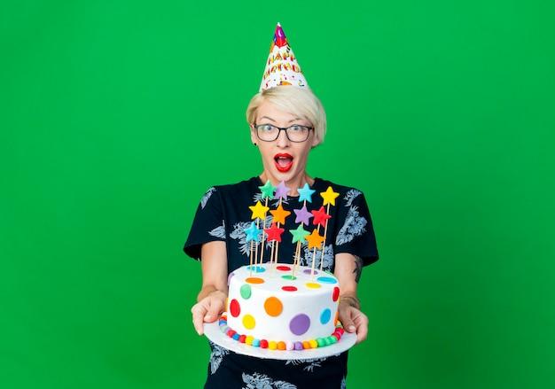 Beeindruckte junge blonde partygirl, die brille und geburtstagskappe trägt, die geburtstagstorte mit sternen ausdehnt, die kamera lokalisiert auf grünem hintergrund mit kopienraum betrachten