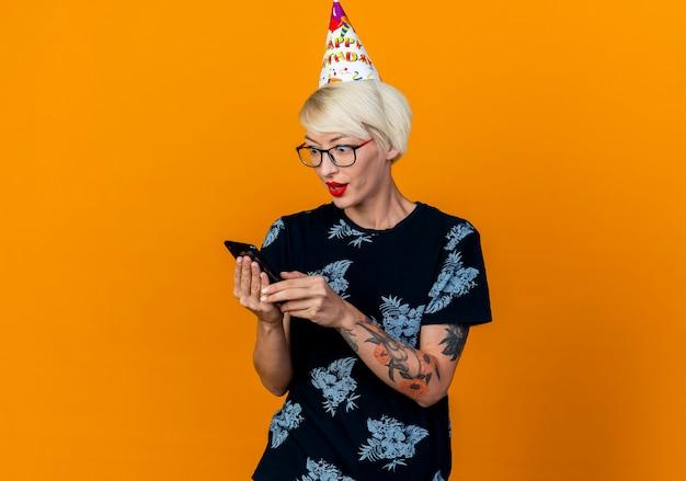Beeindruckte junge blonde partygirl tragen brille und geburtstagskappe halten und betrachten handy lokalisiert auf orange hintergrund mit kopie raum