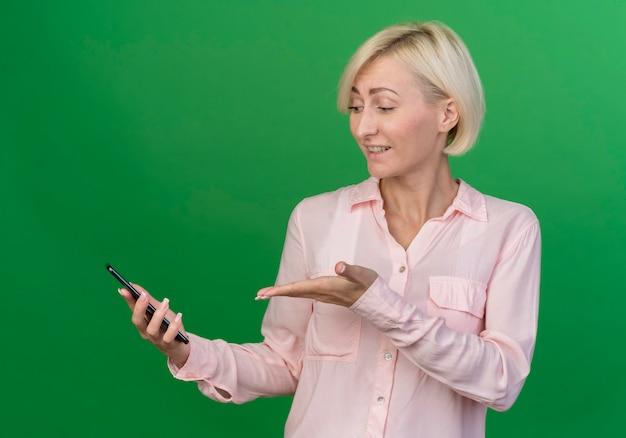 Beeindruckte junge blonde slawische frau, die das betrachten und zeigen mit der hand auf handy lokalisiert auf grünem hintergrund hält