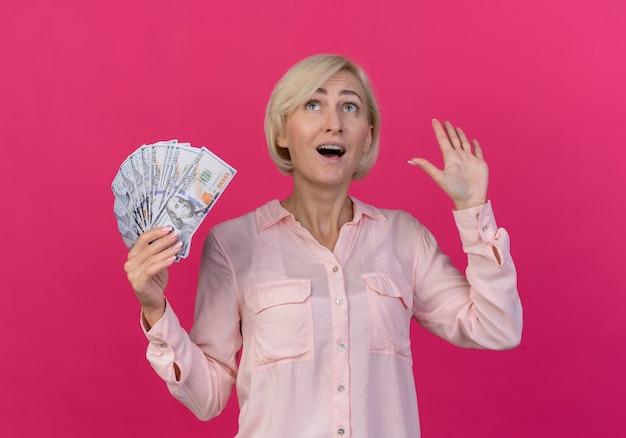 Beeindruckte junge blonde slawische frau, die geld hält, das leere hand zeigt und lokalisiert auf rosa hintergrund schaut