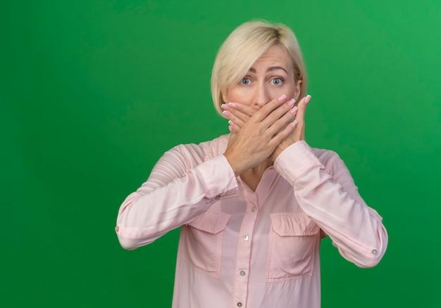 Beeindruckte junge blonde slawische frau, die hände auf mund lokalisiert auf grünem hintergrund mit kopienraum setzt