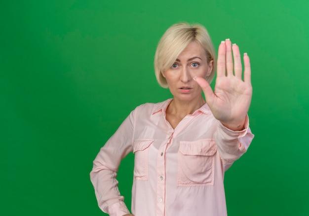 Beeindruckte junge blonde slawische frau, die kamera betrachtet und stoppgeste lokalisiert auf grünem hintergrund mit kopienraum tut