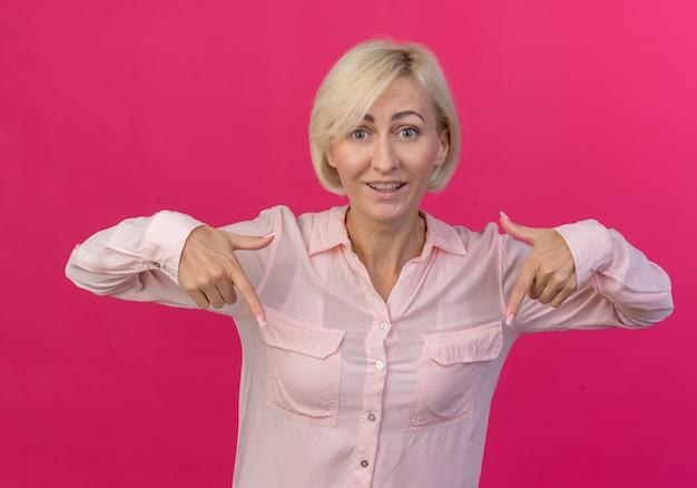 Beeindruckte junge blonde slawische frau, die lokalisiert auf rosa hintergrund zeigt