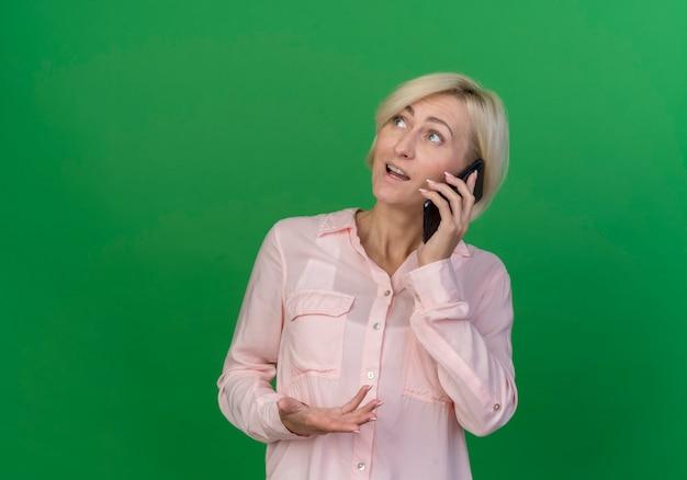 Beeindruckte junge blonde slawische frau, die nach oben spricht und am telefon spricht, hält hand in der luft lokalisiert auf grünem hintergrund mit kopienraum
