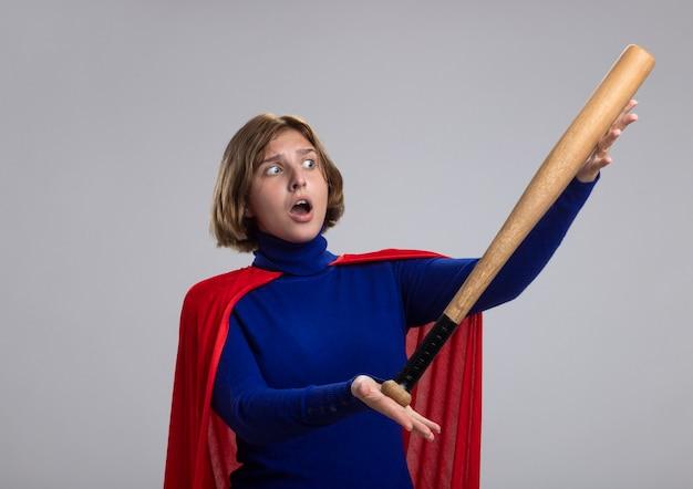 Beeindruckte junge blonde superfrau im roten umhang, der baseballschläger lokalisiert auf weißer wand hält und betrachtet